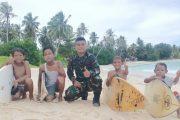 Keseruan Satgas TMMD Bermain Surfing Bersama Anak-Anak di Pantai Mapaddegat